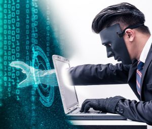 a masked individual in a suit putting his hand inside of a silver laptop as a metaphor for entering the cyber world to steal data