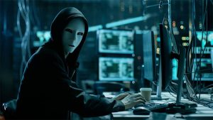 An image featuring a person wearing a mask and using his computer representing a hacker